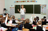 The teacher explains to children a lesson at school near a board — Stock Photo