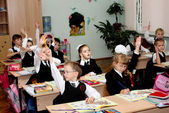 Children at school at a lesson lift hands — Stock Photo