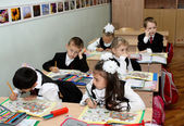 Children at school at a lesson write in writing-books — Stock Photo
