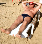 The man in dark glasses sunbathes on a beach — Stock Photo