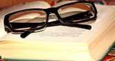 Spectacles on revealled to book — Stock Photo