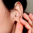 Stock Photo: Womtouches by fingers of hand of lobe of ear