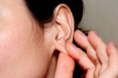 The woman touches by fingers of a hand of a lobe of an ear — Stock Photo