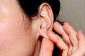 žena se dotýká prsty ruky lalůček ucha — Stock fotografie