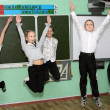Children jump in class near blackboard — Stock Photo #18128381