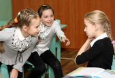 Three girls talk at school at a lesson — Stock Photo