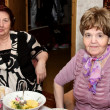 Stock Photo: Two elderly women sit at a dining table