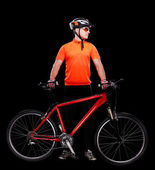 Cyclist on black background holding the bicycle — Stock Photo