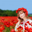 Beautiful girl in a poppy field — Stock Photo