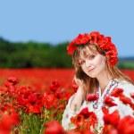 Beautiful girl in a poppy field — Stock Photo