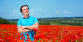 Young man standing in poppy field — Stock Photo