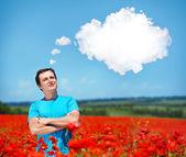 Young man standing in a poppy field — Zdjęcie stockowe