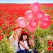 Mother and daughter in a poppy field — Stock Photo #26836671