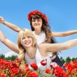 Stock Photo: Mother and daughter in a poppy field