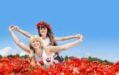 Mother and daughter in a poppy field — Stock Photo