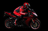Motorcyclist in red equipment — Stock Photo