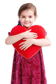 Girl in red dress holding the heart cushion — Foto de Stock