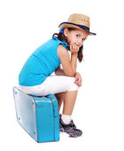 Little girl sitting on the blue suitcase — Stock Photo