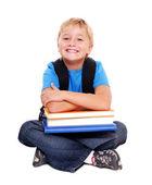 Happy schoolboy sitting on the floor — Stock Photo