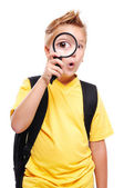 Schoolboy holding the magnifying glass — Stock Photo
