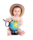 Baby boy holding the magnifier glass and the globe — Stock Photo