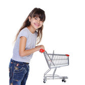 Girl holding shopping trolley side view — Stok fotoğraf