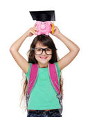 Schoolgirl holding piggy bank with mortar board — Stock Photo