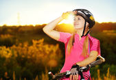 Cycling girl looking to the sunset — Stock Photo