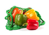 Fresh sweet peppers in a green string bag — Stock Photo