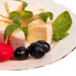 Cheese plate with black grapes and green basil — Stock Photo