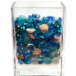 Blue glass pebbles and seashells in the glass — Stock Photo