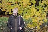 Mature woman near autumn tree — Stock Photo