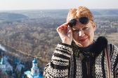 Portrait of a mature woman, slightly lifting sunglasses — Stock Photo