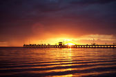 Sunset over a wooden pier — Stock Photo