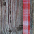 Wooden background with a checked ribbon — Stock Photo