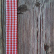 Wooden background with a checked ribbon — Stock Photo #43028115