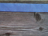 Wooden background with a checked ribbon — Fotografia Stock