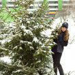 Winter girl behind snow tree — Stock Photo