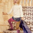 Blonde girl 3 years old  standing with shopping — Stock Photo