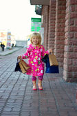 3 years old girl down the street with shopping — Stock Photo