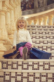Girl 3 years old sitting with shopping — Stock Photo