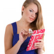 Girl in a blue dress unpacks Christmas gift — Stock Photo