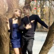 Young couple standing on a tree — Stock Photo