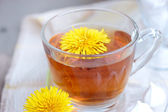 Tea in glass cup and flowers — Stock Photo