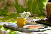 Gofret ve laptop yanında çay yuvarlak — Stok fotoğraf