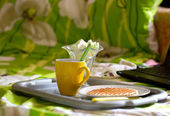 Round wafers and tea near laptop — Stockfoto