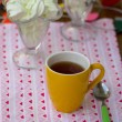 Tea in yellow cup with candy - Stock Photo