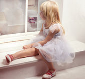 Girl 3 years old in a white dress near window — Stock Photo