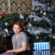 Stock Photo: Girl with present near the Christmas tree
