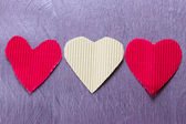 Three paper hearts on the purple board — Stock Photo